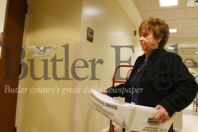 Harold Aughton/Butler Eagle: Kathleen Treeme, a temporary worker at Butler's bureau of elections, carries a mail flat full of ballots into the center where the ballots are sorted, Monday afternoon, May 11, 2020.