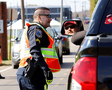 Cpl. Jack Ripper of the Penn Township Police Department directs a motorist at a security line outside of the Pittsburgh Butler Regional Airport prior to President Trump's campaign rally. Seb Foltz/Butler Eagle