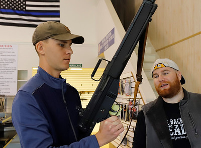 Nate Svoboda of Butler looks at a vintage HK-91 rifle with Kurt Hunka of Down Range Supply Friday at the Evans City Road store. Seb Foltz/Butler 10/02/20