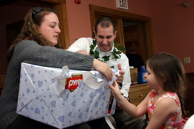 Adam and Kristen, with the help of Melanie open a gift at their shower.