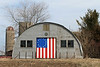 """Quonset Hut on the Prairie"" - Daily Photo - 05/18/13<br /> <br /> Having spent some time in Quonset Huts while in the Marine Corps., this building held some nostalgia for me.  Nice to see it put to use.  You may remember these from World War II photos, films in the 1950s or Gomer Pyle.  Surprised to see an organization formed focused on these structures and the hyperbole is a little over the top, though they are trying to sell a book.  Hope you enjoy!<br /> <br /> <br /> <a href=""http://www.quonsethuts.org/index.htm"">http://www.quonsethuts.org/index.htm</a><br /> <br /> The Book:<br />  <br /> Quonset Hut: Metal Living For A Modern Age tells the story of this unique architectural phenomena, from its birth during WWII as a mass-production shelter to its new status as an icon of American pragmatism, ingenuity, perseverance, and individuality.<br /> <br /> When World War II came along, the American military found itself in need of a prefabricated, lightweight shelter that could be easily shipped and quickly assembled. The Quonset hut, that sliced tube of corrugated metal, was the answer. More than 153,000 were produced as part of the war effort. In its aftermath, even more were built and existing huts were adapted to house the postwar population boom. Of course, it couldn't last: the American desire for permanence meant decay and neglect for many of these rough-and-ready shelters and quickie warehouses.<br /> <br /> But in the midst of its almost tragic tale of extinction, the Quonset hut has emerged as an unexpected icon of Americana and an oasis of architectural imagination. Travel the back roads of America and you will find the Quonset's distinctive shape enclosing everything from houses of worship to houses of pancakes.<br /> <br /> Quonset Hut tells the story of this unique architectural phenomena, from its birth during WWII as a mass-production shelter to its new status as an icon of American pragmatism, ingenuity, perseverance, and individuality."