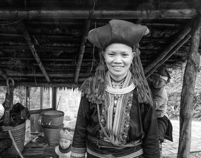 28-04-2013: People of Vietnam. Young Red Dao lady smiling after having sold me a piece of embroidered fabric.