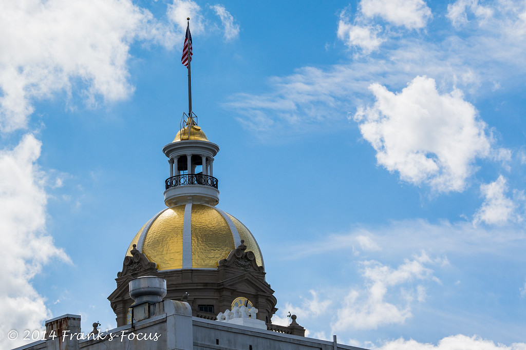 April 18, 2014 -- Dome of City Hall in Savannah, GA.<br /> Savannah's City Hall was built in 1905 and its gold dome has become an icon for the City.  Savannah's City Hall is the most distinctive building in town with its clock tower topped with a gold dome and a towering American flag. It's interesting to note the dome was historically copper, but was coated in gold leaf as recently as 1987.