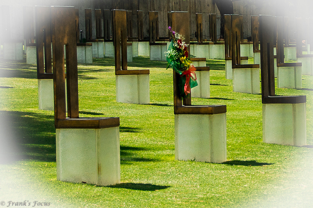 ".<br /> Today is the 22nd Anniversary of the bombing of the Murrah Federal Buildiing in Oklahoma City, Oklahoma.<br /> <br /> This photo is from the ""Field of Chairs"" at the memorial, highlighting one chair that some family member has decorated in memory of a loved-one lost in the bombing.<br /> <br /> The Field of 168 Empty chairs lies within the footprint of the Alfred P. Murrah Federal Building.  Each empty chair is etched with a name of a victim to stand as a reminder of the innocent lives that were lost. The emptiness of the chair expresses a sense of absence. There are  five western chairs, separated from the larger group, represent those not inside the building, but who lost their lives as a direct result. The other 163 chairs are arranged in a pattern of nine rows according to the floors of the building. Each persons chair is then listed in alphabetical order according to the agency in which they worked or were visiting. The glass base of each chair illuminates at night emphasizing the individual's name.The light delivers comfort from and eliminates the fear of the darkness. As a unit the empty chairs are arranged to represent the damage done to the building, with the highest concentration of chairs near the center of the footprint to symbolically fill in the damage done to the building by the bomb. And, as you look out over the field, you will notice two sizes of chairs. The large chairs represent the adults and the smaller chairs the nineteen children whose lives were taken. Again, reminding us all of the impact this bombing had on this community and this nation."
