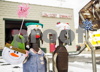 Robert Layman / Staff Photo A pair of muffler statues sport their festive wear and embrace the impending cold winds by holding pinwheels outside the Low Cost Exhaust shop in Rutland Wednesday afternoon.