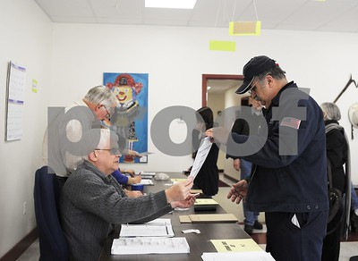 Robert Layman / Staff Photo A voter recieves his ballot at the Castleton Fire Department Tuesday morning.