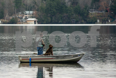 Robert Layman / Staff Photo  A man fishes with is dog on the cold late autumn waters of Lake Bomoseen Sunday afternoon Nov 27 2016