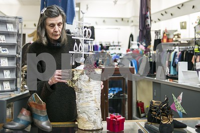 Robert Layman / Staff Photo  ChristineTattersall  arranges merchandise in her store Wednesday afternoon.