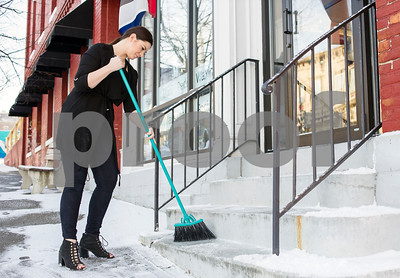 Robert Layman / Staff Photo  Paige Carrara, owner of Blush Salon & Beauty Lounge, makes a quick dash outside in the brisk morning to sweep off the drifting snow from the steps of her storefront Thursday.