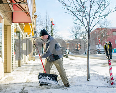 Robert Layman / Staff Photo  Tim Schneller, owner of Timco Jewlers, shovels off the snow from the sidwalk outside his storefront Wednesday morning.