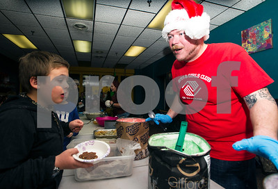 Robert Layman / Staff Photo  It's dessert time at the Rutland County Boys and Girl's Club annual holiday dinner Tuesday night and Chance Wendell, left, has a jaw dropping experience as Jesse Flanders, right, goes through the many options of various ice creams and cookie assortments.
