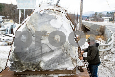 Robert Layman / Staff Photo  Albert Gawet, of Gawet Marble and Granite, unchains a 14-ton block of marble off of a tractor trailer flat bed Tuesday morning.