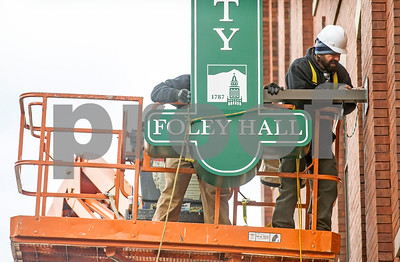 Kevin Lafaso, right, of Balestra Building and Remodeling, attaches the bottom part of the new sign for Castleton University's Foley Hall in downtown Rutland Tuesday morning.