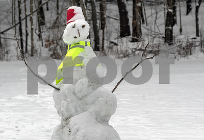 Robert Layman / Staff Photo A fashionable snowman sits in a field off Whipple Hallow Road, decorated with a high-visibiltiy vest and a festive red bucket head.