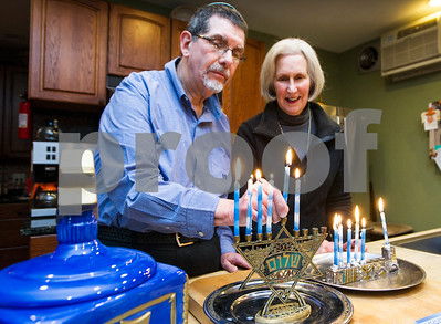 Robert Layman / Staff Photo  Gathered around their menorah given to them at their wedding 44 years ago, Steve Brenner, left, and his wife Leslie light candles  for the fifth night of Hanukkah at their home in Rutland Wednesday.