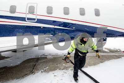 Robert Layman / Staff Photo Bryan Keefe, of Rutland Southern Vermont Regional Airport pulls in a fuel hose after filling up a jet during the winter storm Thursday morning.
