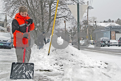 Robert Layman / Staff Photo As the snow from Thursday's winter storm falls, Anthony Horton tries to stay ahead it by keeping the sidewalks clear outside of Gill's Delicatessen.