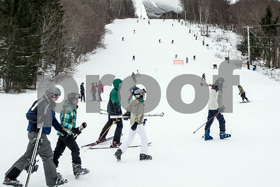 Robert Layman / Staff Photo A group of skiers walk to the Golden Express chairlift at Pico Mountain Friday afternoon.