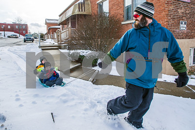 Robert Layman / Staff Photo Although the snow off most sidewalks in Rutland City has been cleared, that doesn't stop Alderman Chris Ettori, right, from towing his two sons Nicholas, front, and Liam around for some urban sledding on the remaining white patches as the trio travels across town to visit family.