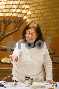 Robert Layman / Staff Photo Rebbetzin Jessica Weber, right, lights the candle to begin the ceremony.
