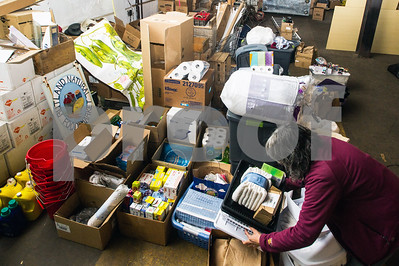 Robert Layman / Staff Photo Carol Tashie, right, organizes household items donated by members of the Rutland community and beyond for the incoming Syrian and Iraqi refugees in the warehouse behind the Rutland Area Food Co-Op Wednesday afternoon.