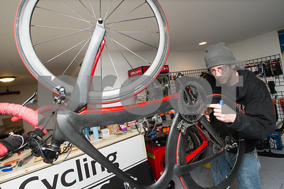 Robert Layman / Staff Photo Scott Cole, owner of Cols Cycling, changes out a set of brake pads on a race bike at his shop in downtown Rutland Thursday afternoon.