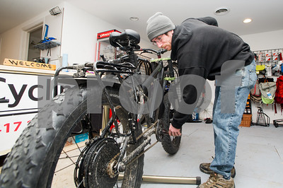 Robert Layman / Staff Photo Scott Cole, owner of Cols Cycling, tunes an electric fat bike at his shop in downtown Rutland Thursday afternoon.