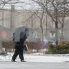 Robert Layman / Staff Photo A pedestrian shields themselves from yesterday's ice storm as they cross over to Merchants Row during the storm Tuesday.