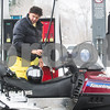 Robert Layman / Staff Photo Andrew Royce checks his fluid levels before filling up and getting back on the snowmobile trail in Pittsfield Wednesday afternoon.