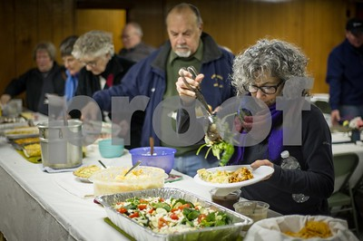 Robert Layman / Staff Photo A woman fills her plate after the Pittsfield annual town meeting Tuesday morning in the bottom of the town hall.