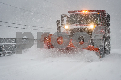 Robert Layman / Staff Photo A plow works on Quarterline Road during Tuesday's snowstorm.