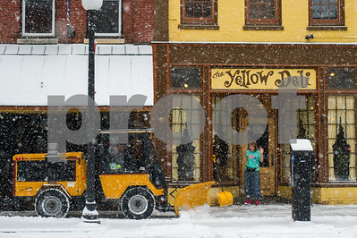 Robert Layman / Staff A woman who was shoveling outside the Yellow Deli in Rutland stops to let a sidewalk plow finish the job during the snowstorm Tuesday morning.