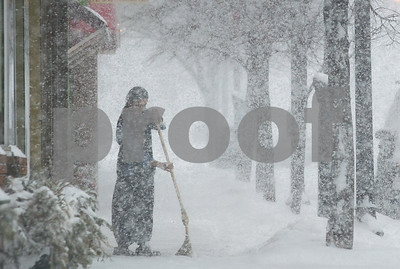Robert Layman / Staff Photo A woman sweeps snow outside of the Yellow Deli in Rutland during Tuesday's blizzard.
