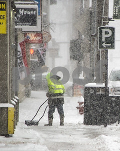 Robert Layman / Staff Photo A snow shovler works to clean out the entrance to the LAZ during Tuesday morning's snowstorm.