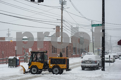 Robert Layman / Staff Photo A sidewalk plow crosses Wales Street during the snowstorm Tuesday morning.