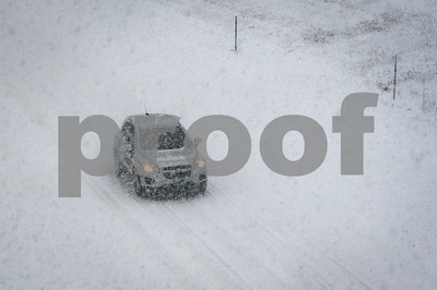 Robert Layman / Staff Photo Tuesday's blizzard brought low visibiltiy and hazerdous driving conditions to the State. Seen here, a car heads on Route 4 east towards Rutland.