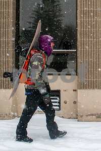 """Robert Layman / Staff Photo As the snow falls rapidly in Rutland, Peter Bezek heads to the bus station with his snowboard strapped to his back to catch the Diamond Express up to Killington Mountain Resort. """"Today's my day off,"""" Bezek said."""