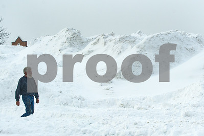 Robert Layman / Staff Photo A man walks by a snow bank piled up in the downtown shopping plaza.