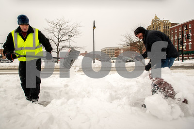 Robert Layman / Staff Photo Bob Fitzpatrick, left, and Jeffrey Selleck of Earth, Waste & Metal shovel snow outside the downtown shopping plaza Wednesday afternoon.