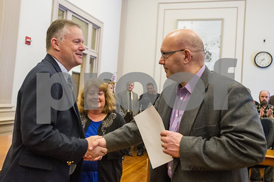 Robert Layman / Staff Photo Rutland City Mayor Dave Allaire, left, shakes hand with City Clerk Henry Heck  after being sworn in during an induction ceremony in City Hall Wednesday morning. Allaire was also joined by his wife Audrey, center.