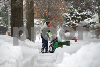 Robert Layman / Staff Photo A man clears a path from a drive way in Rutland Tuesday morning.