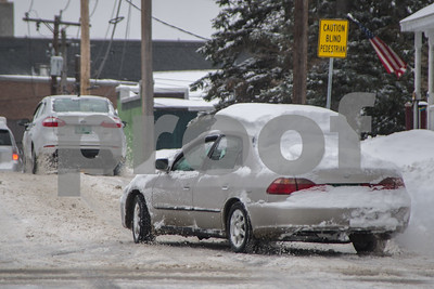 Robert Layman / Staff Photo A car with snow piled on the roof drives turns onto Pine Street Tuesday morning.