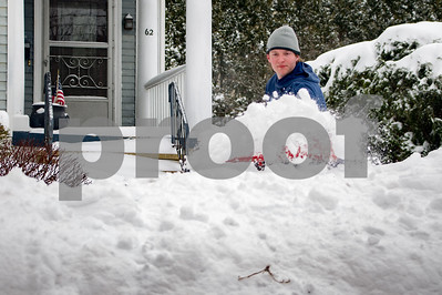 Robert Layman / Staff Photo Bobby Dazi clears hoofs a shovel full of snow onto the snow bank outside his parents house on Church Street Wednesday morning.