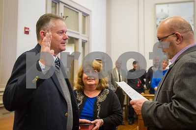 Robert Layman / Staff Photo Recently elected Rutland City Mayor Dave Allaire, left,  takes the mayoral oath Wednesday morning at City Hall. City Clerk Henry Heck, right, swore Allaire in while his wife, Audrey, center, held the Bible.