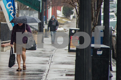 Robert Layman / Staff Photo A woman walks down Strongs Avenue in Rutland yesterday holding an umbrella. What began as snow Friday morning