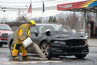 Robert Layman / Staff Photo A first responder from the Rutland  Town Fire Department cleans up a scene from a two car motor vehicle collosion at the intersection of Randbury Road and the Route 7 south Tuesday evening. No injuries were reported in the accident.