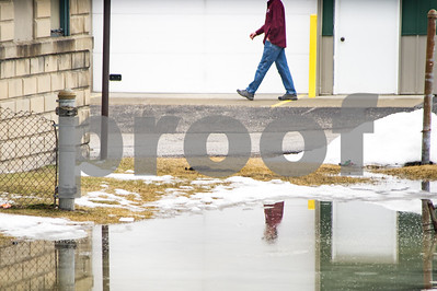 Robert Layman / Staff Photo Snow melt from Tuesday's warm weather caused puddles around Rutland Tuesday. Seen here, a pedestrian walks on higher ground alongside Union Street.