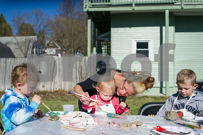 Robert Layman / Staff Photo Miranda Audy, center, helps her daughter Ilivia Gladding, paint a rock along with her brothers, Colton, left, and Logan right, at the Spring Craft Party in Rutland Tuesday afternoon.