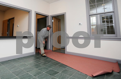 Robert Layman / Staff Photo  Tom Traverse of McLure Construction pulls a roll of protective paper from the floor of the new Town Hall in Castleton. The town staff is expected to move in Friday of this week.