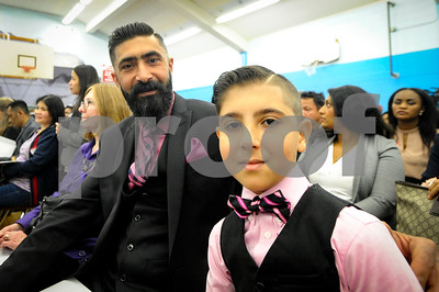 Robert Layman / Staff Photo  Mustafa Jassim sits with his father Ather during a naturalization ceremony at the Neshobe School in Brandon. Jassim, an Essex Junction resident, migrated from Baghdad, Iraq.